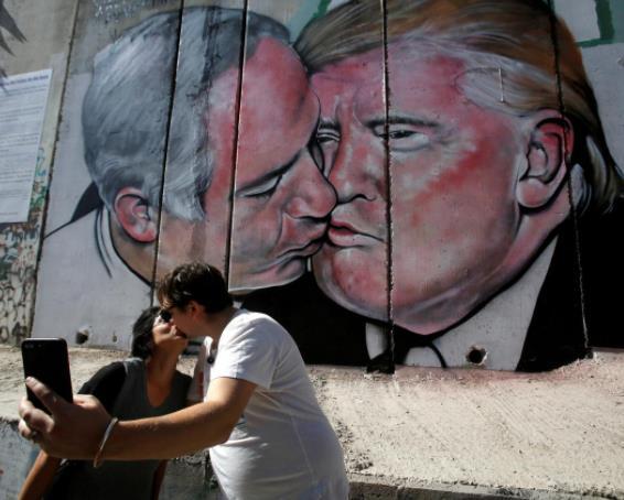 Photo of Donald Trump and Benjamin Netanyahu share a kiss on a wall mural in Bethlehem
