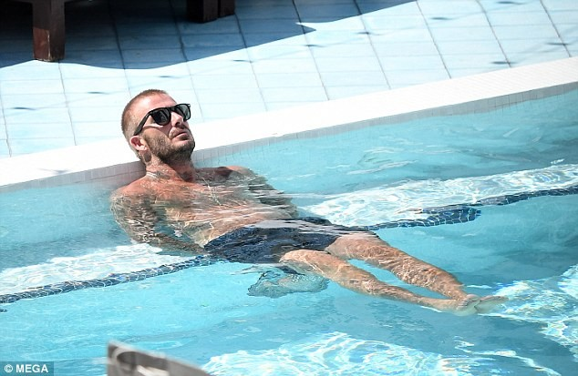 David Beckham flaunts his impressive physique as he relaxes by the pool